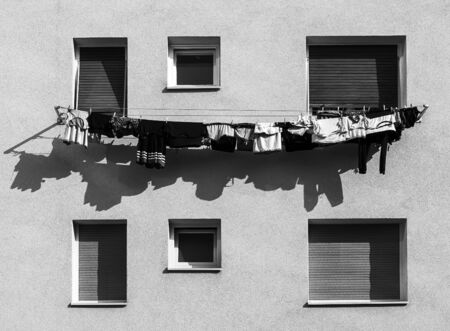Clothes hanging outside of a building and drying out.