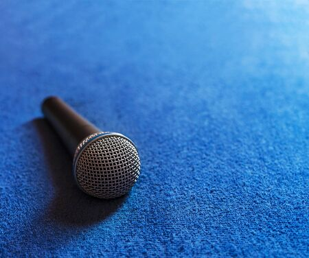 Microphone placed on a blue fabric with blur effect.