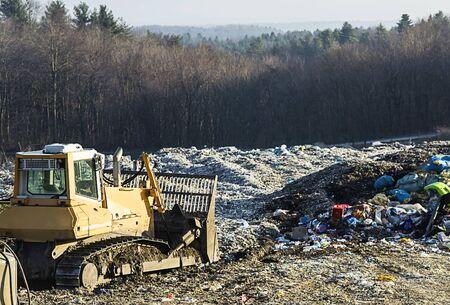 Buldozer e un mucchio di spazzatura di plastica.