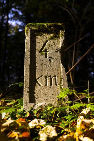 Old stone for distance with carved 4km mark in it. 版權商用圖片