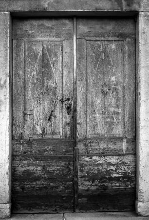 Old wooden door with some details and many signs of ageing.