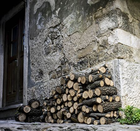 Small pile of wood stacked infront of an old building. 版權商用圖片