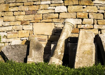 Gravestones lit by sun placed near a wall and abandoned. Stok Fotoğraf