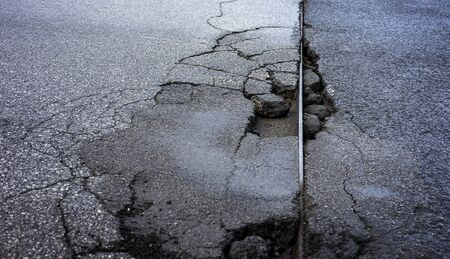 Damaged road that needs some repair work 免版税图像