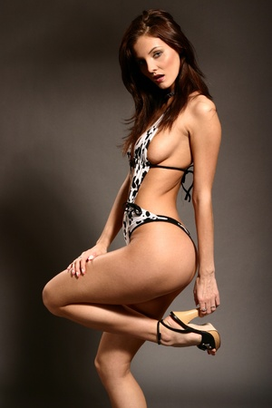 Big breasted brunette model posing in classic swimsuit Stock Photo - 11567474