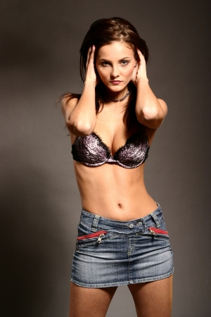 Brunette model posing in studio in skirt and bra photo