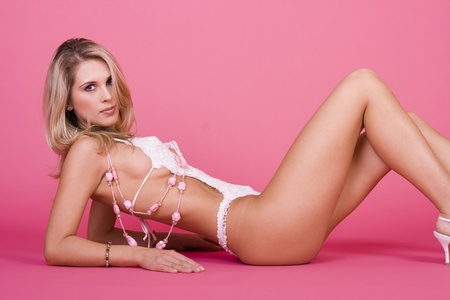 Sexy blonde lingerie woman on pink background