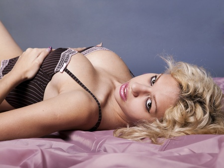 Sexy beautiful young blonde woman in corset on pink satin blanket photo