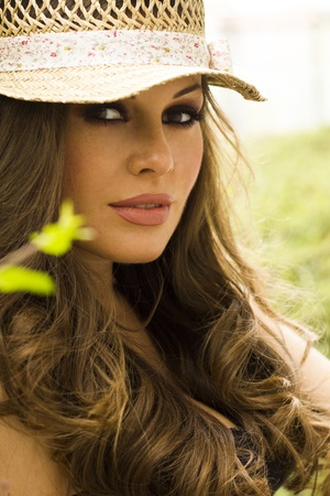 Happy beautiful brunette woman in a park wearing hat  photo