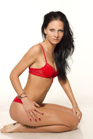 Beautiful sexy slim woman kneeing in red lingerie on white isolated background  photo