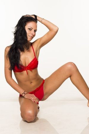 Beautiful sexy brunette slim woman in red lingerie posing on white isolated background