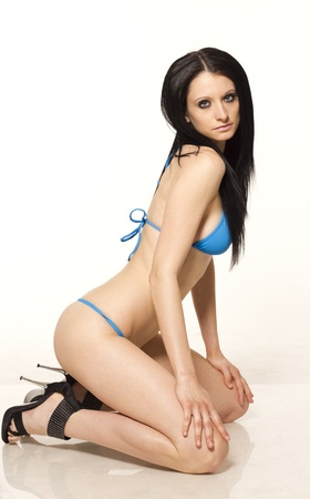 Sexy black haired slim woman in blue micro bikini on white isolated background