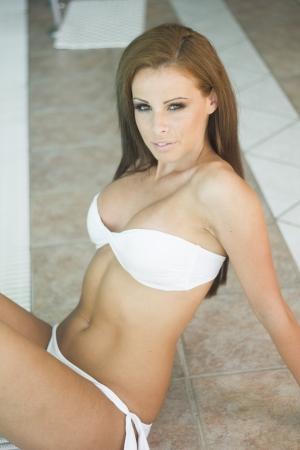 voluptuosa: Hermosa mujer en bikini blanco en una piscina Foto de archivo