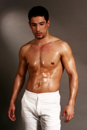 Muscular young man posing in white trousers
