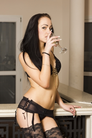 Brunette slim lingerie woman drinking champagne photo