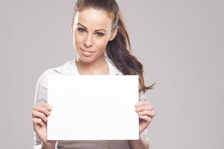 Beautiful brunette business woman with blank sign photo