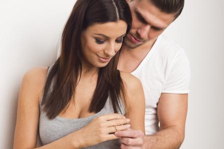 anillo de compromiso: Joven pareja d�ndose un anillo de compromiso Foto de archivo
