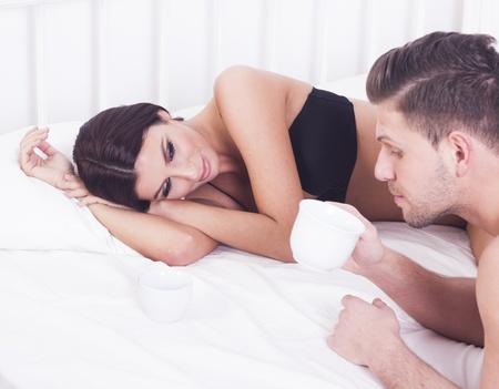 Young couple with cup of coffee in bed photo
