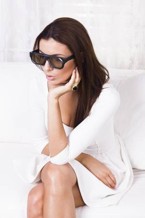 Beautiful woman watching tv in 3d glasses photo
