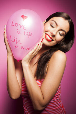 Sexy woman with valentines day balloon on pink background Standard-Bild