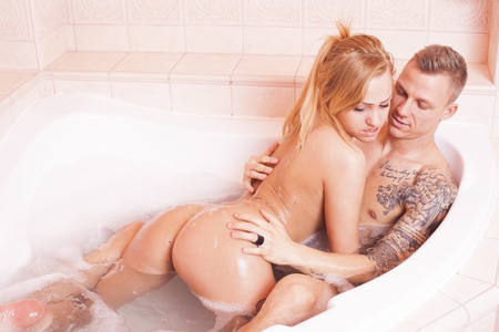 Sexy young nude couple embracing in foam bath