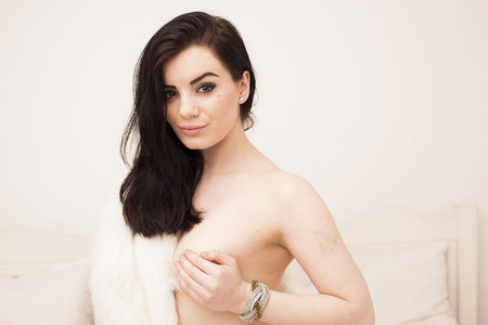 Sexy brunette nude woman wearing white fur coat on the bed photo