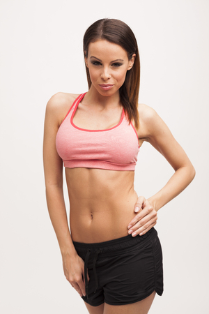 Beautiful brunette fitness woman posing on white isolated  Standard-Bild