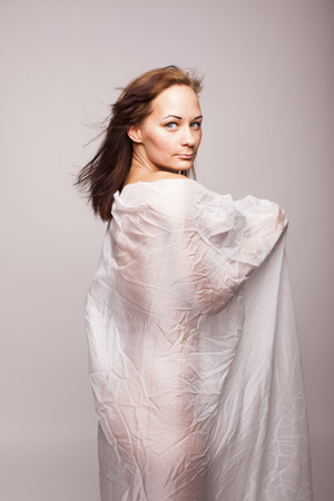 Sexy brunette woman with perfect body covered with white transparent textile on gray isolated background