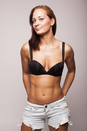 Sexy brunette fitness woman with perfect body on gray isolated background Standard-Bild