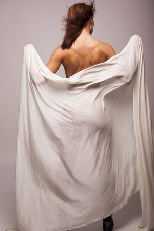 Sexy brunette woman with perfect body covered with white transparent textile on gray isolated background photo