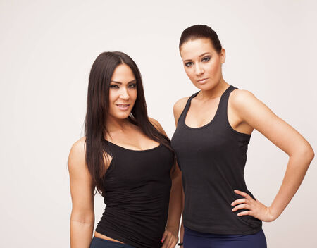 Two sexy brunette fitness women on white isolated background