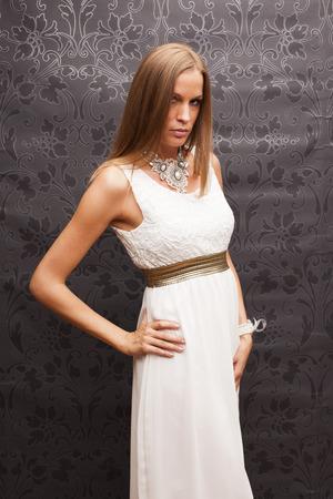 Slim blonde woman in elegant dress on vintage background Standard-Bild