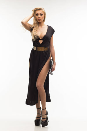 Sexy slim blonde woman in elegant black dress on white isolated background Standard-Bild