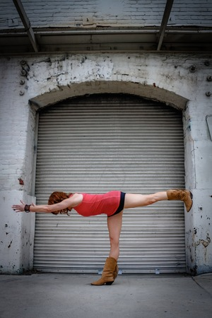 An urban Yogi meditates and practices outdoor yoga outside in the city
