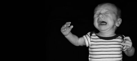 A 3 Week Old Baby Poses on a Black Background. Perfect for Memes with Copy Space.