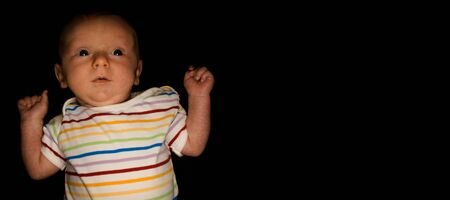 A 2 Month Old Baby Poses on a Black Background. Perfect for Memes with Copy Space. Imagens