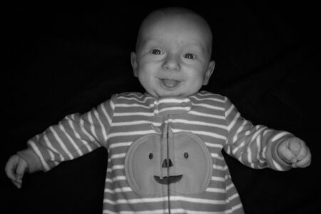 A Three Month Old Baby Poses on a Black Background. Perfect for Memes with Copy Space. Imagens