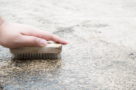 houseclean: Cleaning an outdoor floor in a house area by brushing with a brush Stock Photo