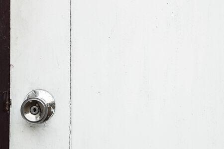 An alloy metal door knob on a white wooden door