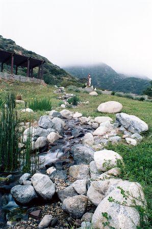 丘の頂上にイエス ・ キリストのはりつけの描写と、丘を下って来る水の流れ
