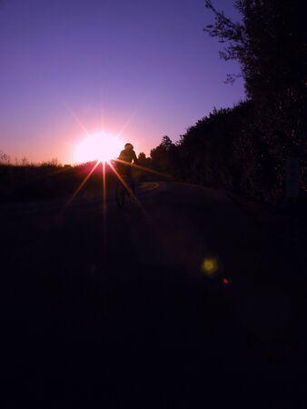 日の出の自転車に乗る 写真素材