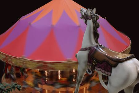 A hobby horse above a merry-go-round with people riding on it.
