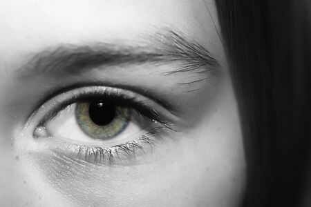 A black and white conversion of a persons eye, with one layer erased in the iris area to accentuate the eye color