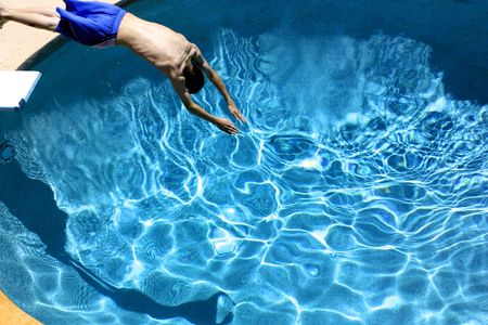 board shorts: A boy diving into a swimming pool