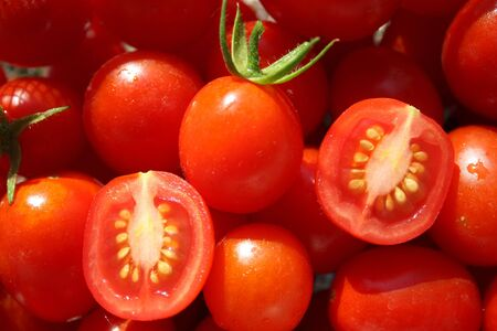 ripened: A bowl of tomatos, with one cut into halves showing the seeds