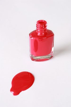 A bottle of red nail polish isolated against white