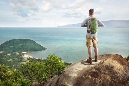 Young man with a backpack overlooking a tropical bay