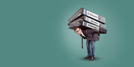 Man carrying a giant stack of tax folders