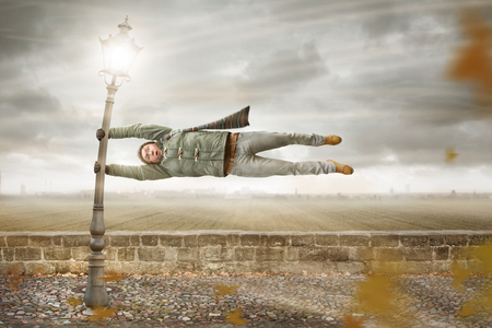Funny man gets blown away by a storm Stockfoto