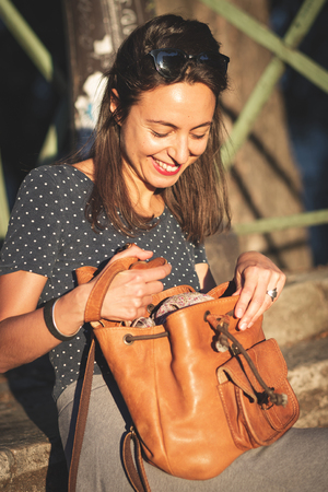 Smiling woman opening a backpack while sitting